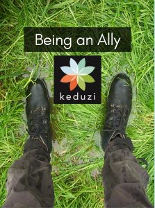 """Someone's legs and booted feet standing in water-logged grass. The words """"Being an Ally"""" are over the image, along with the Keduzi logo, which is a colourful flower."""