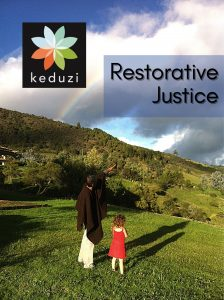 """An older male-presenting person in a Colombian ruana is standing with a small female-presenting child as they look up a mountain at a rainbow in front of clouds. The words on the image say """"Restorative Justice"""" and the Keduzi logo is there, which is a colourful flower."""