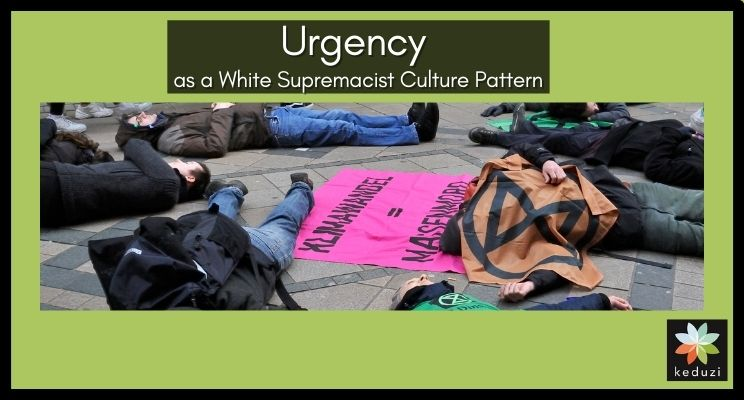 """A photo of Extinction Rebellion activists performing a """"die-in"""" in Germany. They are lying down on a pedestrianised part of a city centre, pretending to be dead. There are Extinction Rebellion symbols on flags. Over the image are the words """"Urgency as a White Supremacist Culture Pattern"""". Also, the Keduzi logo, which is a colourful flower, is in the bottom right-hand corner."""