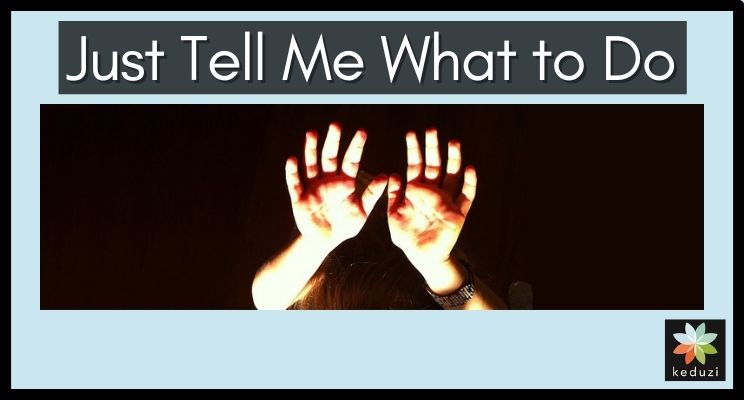 """A child's hands are raised up and lit up against a dark backdrop. You can barely see the top of a head and a bracelet on one wrist. The words over the image are """"Just Tell Me What to Do"""". The Keduzi logo, which is a colourful flower, is also over the image."""