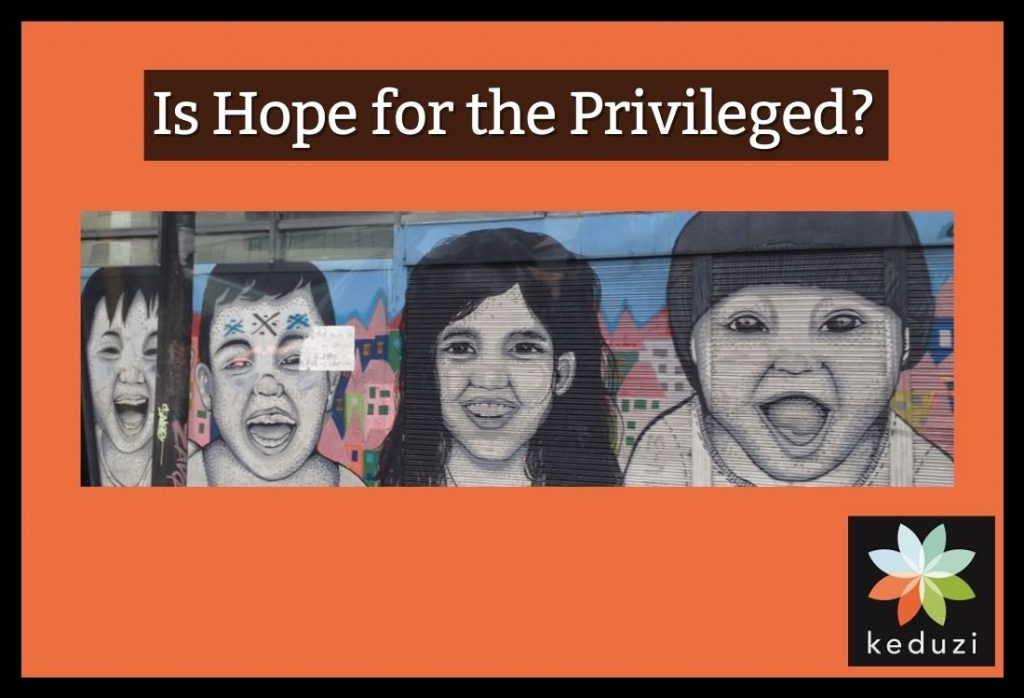 """A mural in Bogotá, Colombia with the faces of children smiling. This image is set against an orange background with the words """"Is Hope for the Privileged?"""" In the corner is the Keduzi logo, which is a colourful flower."""