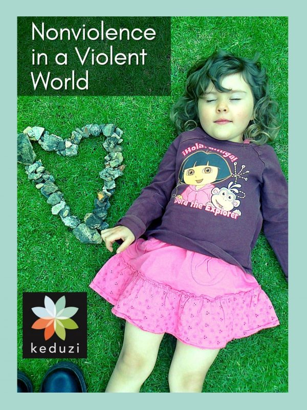 """A young female-presenting child is lying on grass with her eyes closed. Next to her is a heart made out of lots of gray-ish stones. Over the image are the words """"Nonviolence in a Nonviolent World"""" and the Keduzi logo, which is a colourful flower."""